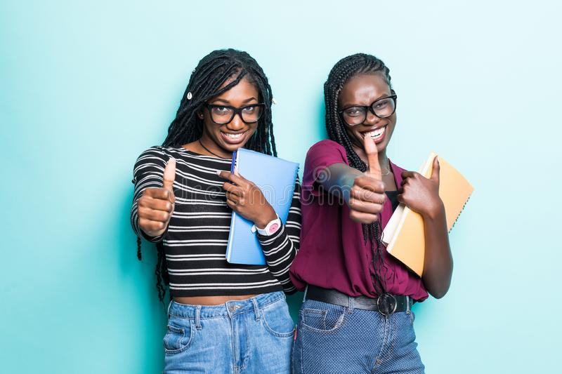 Portrait of two african young school teenage girls holding copybooks and showing thumbs up  over blue background stock images