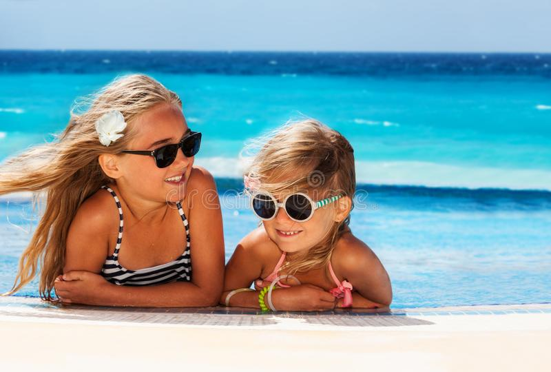 Cute girls sunbathing at the edge of swimming pool. Portrait of two age-diverse blond girls in sunglasses, sunbathing at the edge of swimming pool royalty free stock photography