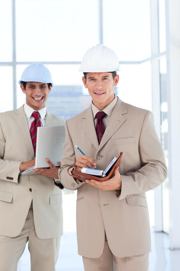 Portrait of two architects wearing hard hat royalty free stock image