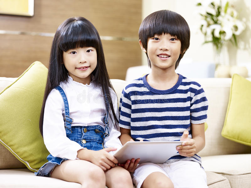 Portrait of two asian children. Sitting on couch holding digital tablet at home stock image