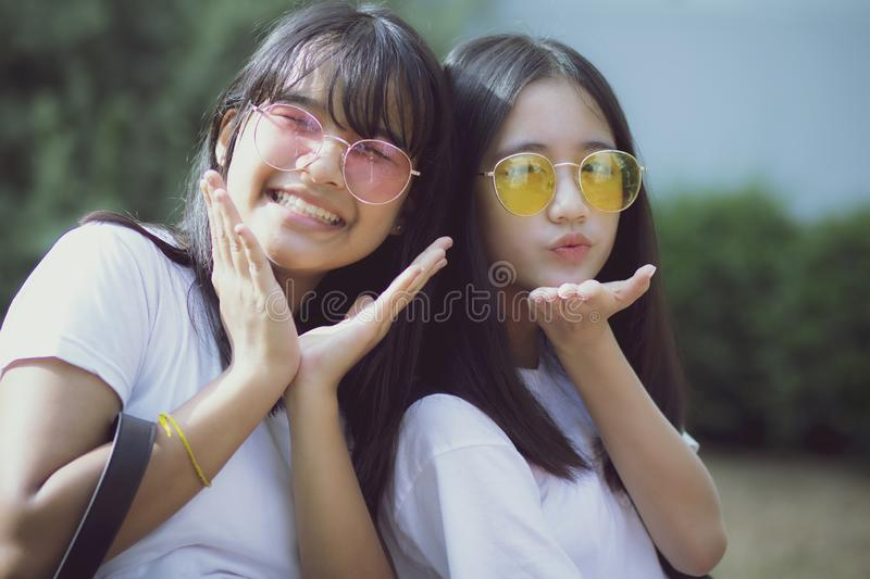 Portrait of two asian teenager relaxing with happiness in green park royalty free stock photography