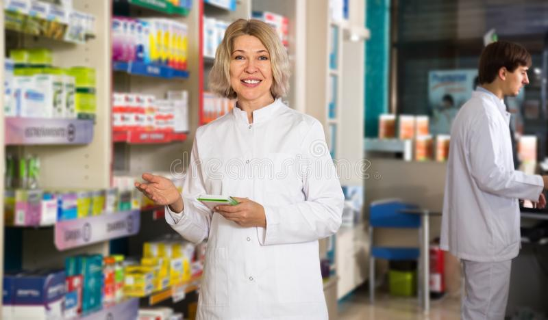 Portrait of two attentive pharmacists. Working in modern farmacy royalty free stock photography