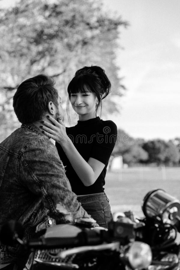 Portrait of two Attractive Good Looking Young Adult Modern Fashionable People Guy Girl Couple on Classic Green Motorcycle Hugging royalty free stock photo