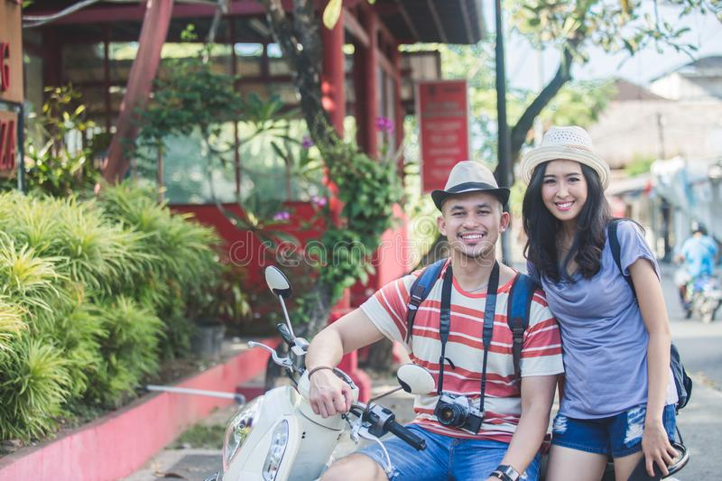 Two backpackers with summer hat smiling to camera while sitting. Portrait of two backpackers with summer hat smiling to camera while sitting on motorbike stock photography