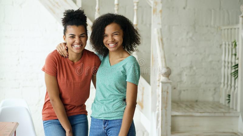 Portrait of two beautiful african american girls laughing and looking into camera at home stock photography