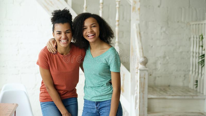 Portrait of two beautiful african american girls laughing and looking into camera at home royalty free stock image