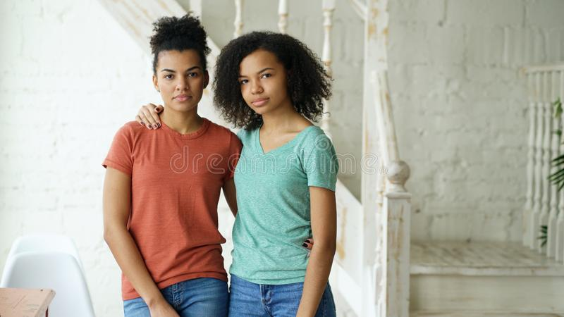 Portrait of two beautiful african american girlslooking into camera indoors royalty free stock image
