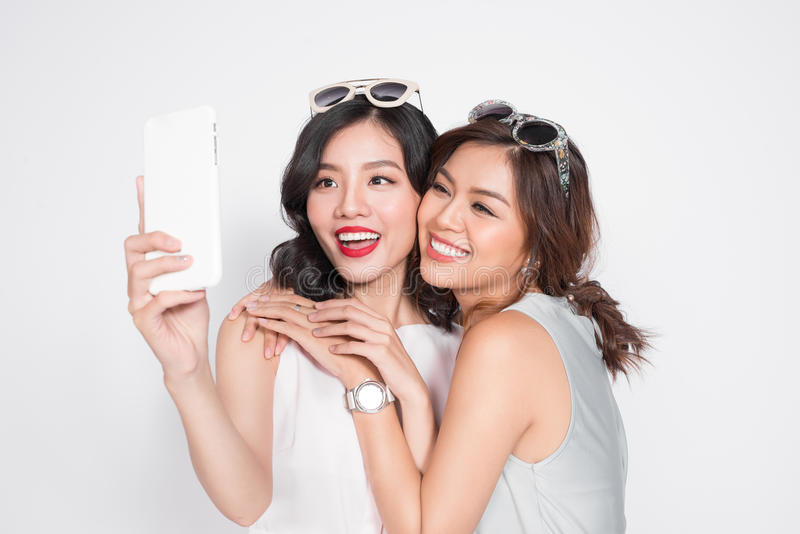 Portrait of two beautiful asian fashionable women taking selfie royalty free stock images