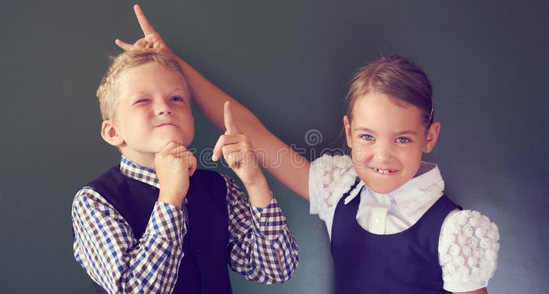 Portrait of two beautiful European kids boy and girl in school uniform standing next to the blackboard. Girl shows horns royalty free stock photography