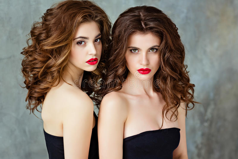 Portrait of two beautiful, glamorous, sensual brunette with gorgeous curly hair and bright makeup with red lipstick, close-up, in royalty free stock images