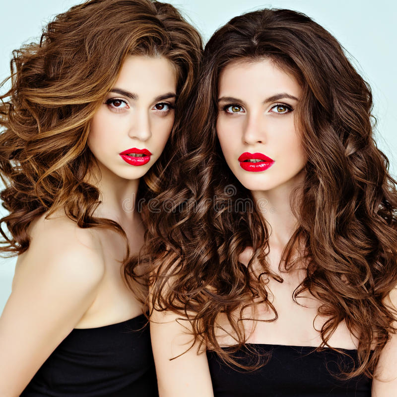 Portrait of two beautiful, glamorous, sensual brunette with gorgeous curly hair and bright makeup with red lipstick, close-up, be. Auty stock image