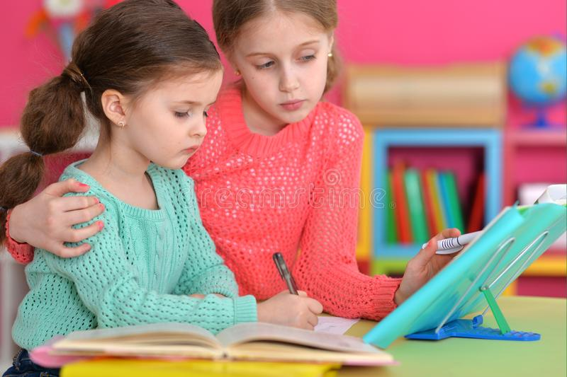 Portrait of two beautiful little girls doping homework royalty free stock images