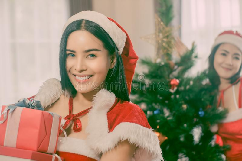 Portrait two beautiful woman holding gift box in hand and wearing red Santa Claus outfit and smiling happily, concept Christmas royalty free stock photo