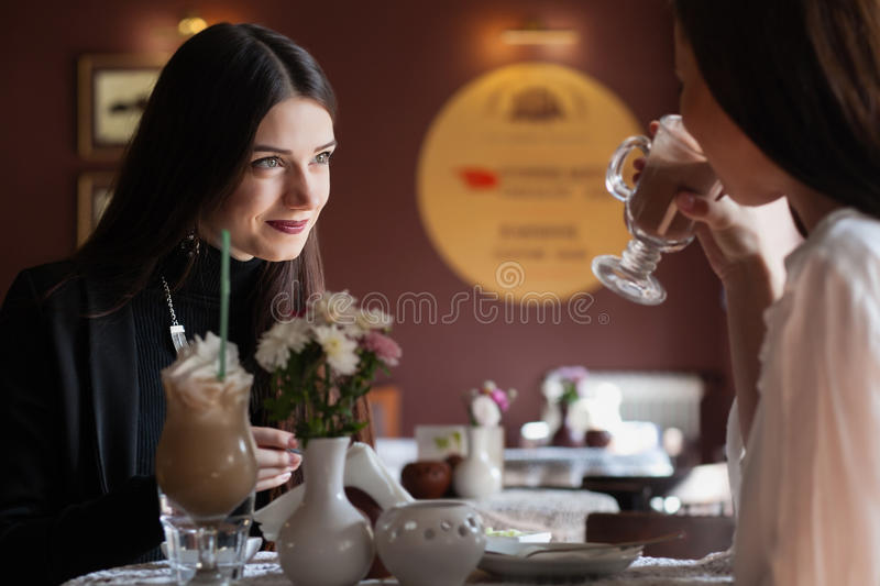 Portrait of two beautiful young girlfriends sitting royalty free stock image