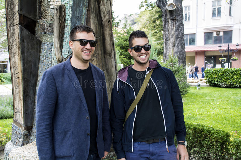 Portrait of two beautiful young men smiling on the street royalty free stock photography
