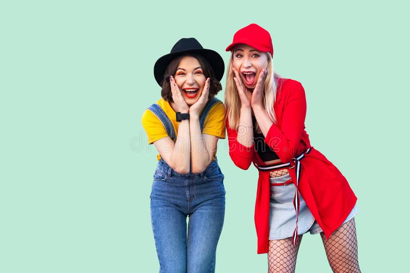 Portrait of two best friend beautiful amazing happy fashionable hipster girls standing and screaming with unbelievable face, stock images