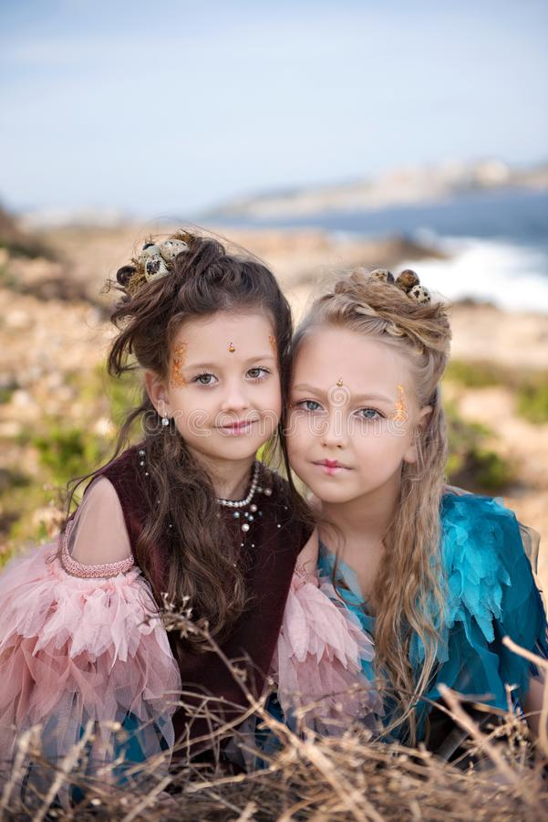 Portrait of two blonde girls and brunettes in fancy dresses of birds and with nests in hairstyles royalty free stock images
