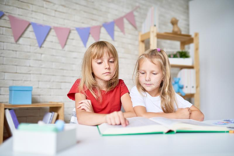 Little Girls Reading Encyclopedia royalty free stock images