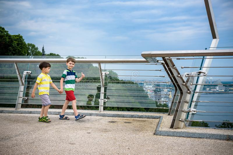 Portrait of two boys kid a walk over a bridge and looking down, child walking outside in sunny day, Young boys relaxing outdoors stock photo