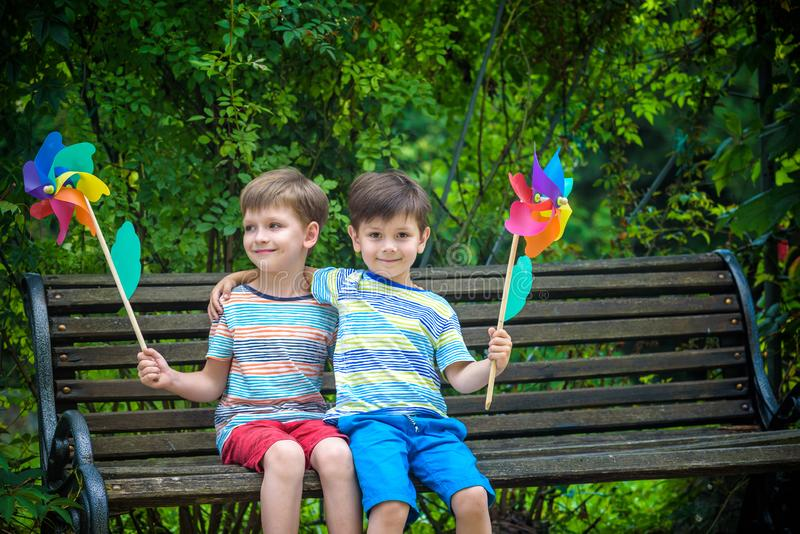 Portrait of two boys, sibling brothers and best friends smiling. Kids sitting on bench play together with pinwheel. Outdoors royalty free stock photo