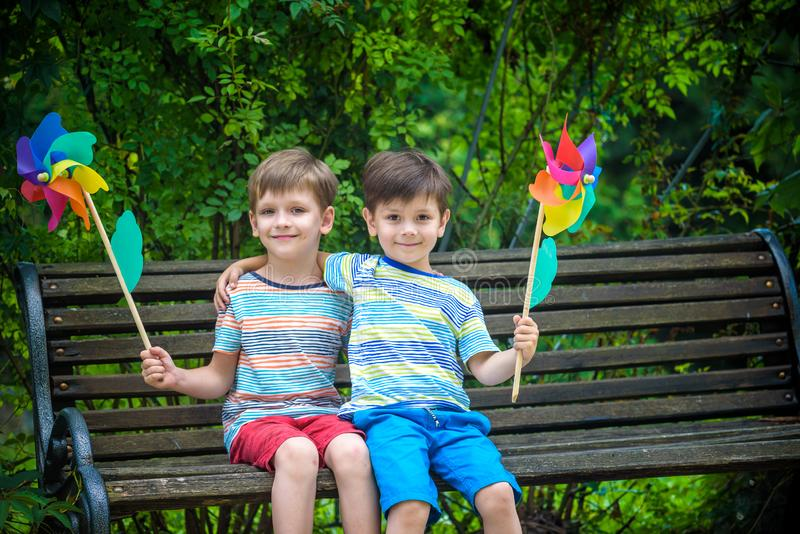 Portrait of two boys, sibling brothers and best friends smiling. Kids sitting on bench play together with pinwheel. Outdoors royalty free stock photos