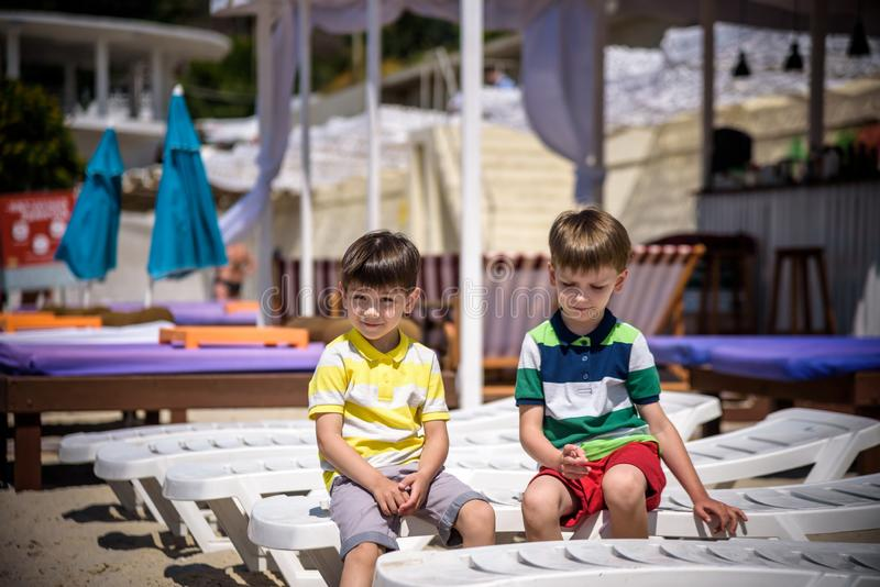 Portrait of two boys sitting on the sunbed at sea beach. Preschool children best friends enjoying summer vacations on sea royalty free stock image