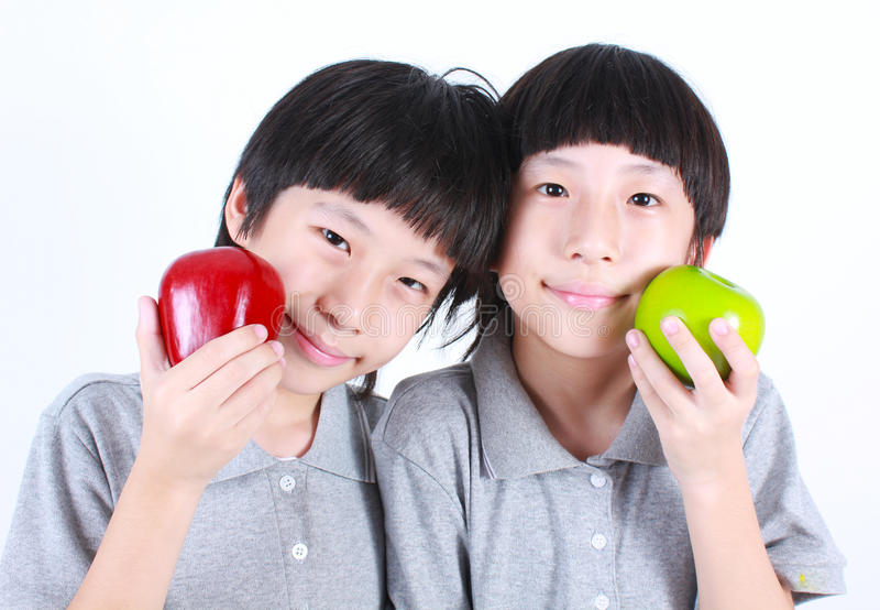 Portrait of two boys, twins holding red and green apples stock image