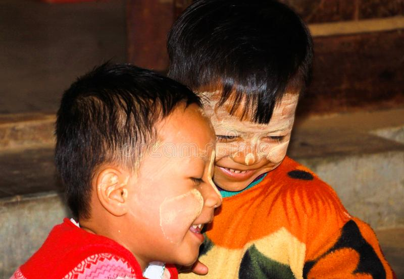Portrait of two burmese happy male children boys with traditional thanaka face painting playing in front of their hut royalty free stock photography