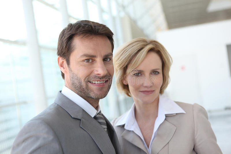 Portrait of two business people indoors. Two smiling business people indoors stock images
