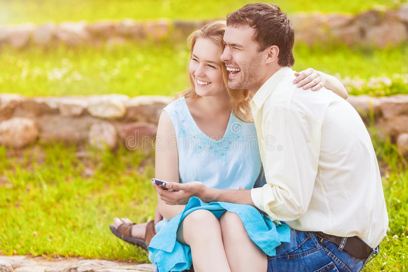 Portrait of Two Caucasian Sweethearts Together Outdoors. Reading royalty free stock photo