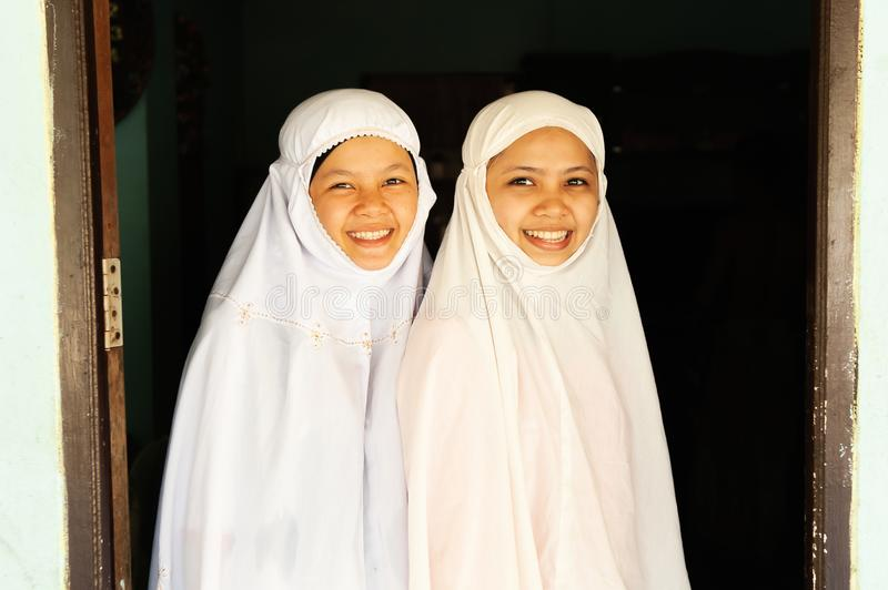 Portrait of two charming Muslim teenage girls in traditional clothing smiling at camera stock image