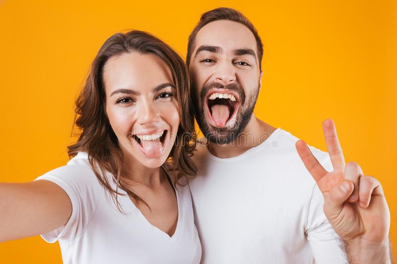 Portrait of two cheerful people man and woman smiling while taking selfie photo, isolated over yellow background royalty free stock photography