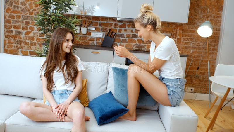 Portrait of two cheerful teenage girlfriends relaxing at home. Portrait of two cheerful teenage girlfriends talking at home while sitting on couch royalty free stock photos