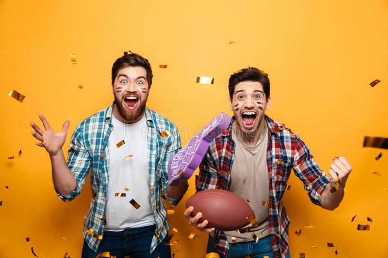 Portrait of a two cheerful young men holding rugby ball royalty free stock images