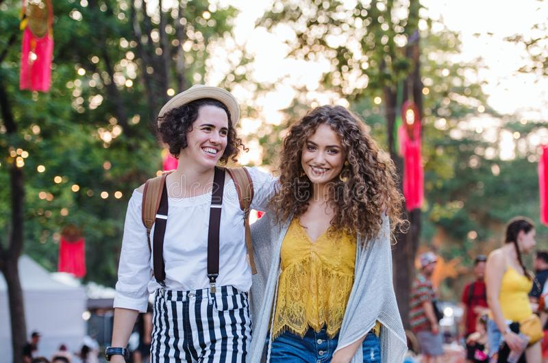 Portrait of two young women friends at summer festival, walking. royalty free stock photo