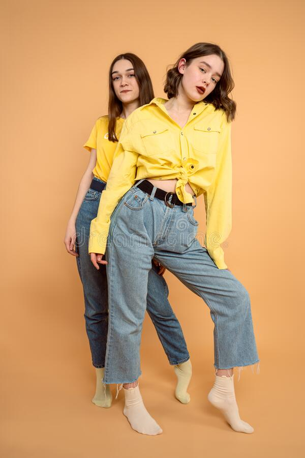 Portrait of two cheerful young women standing together one by one and looking at camera isolated over orange background. Studio photo royalty free stock image