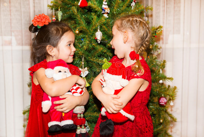 Portrait of two children girls around a Christmas tree decorated. Kid on holiday new year. Portrait of a two children girls around a Christmas tree decorated royalty free stock images