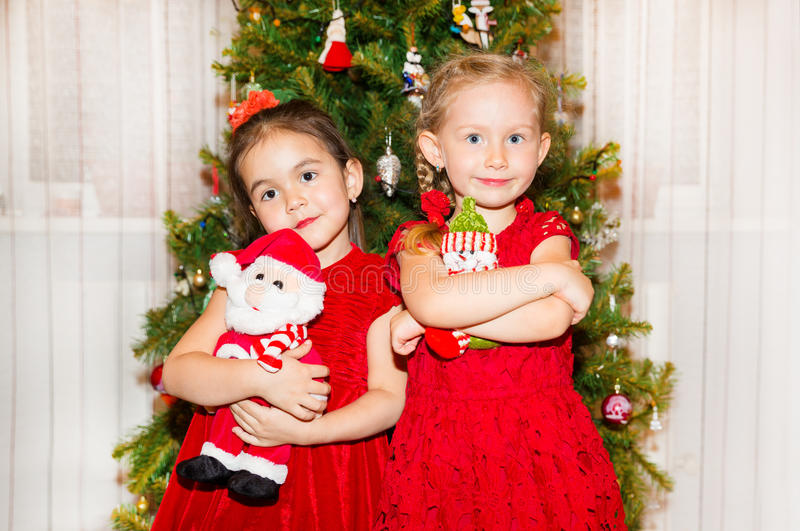 Portrait of two children girls around a Christmas tree decorated. Kid on holiday new year. Portrait of two children girls around a Christmas tree decorated. Kid stock images