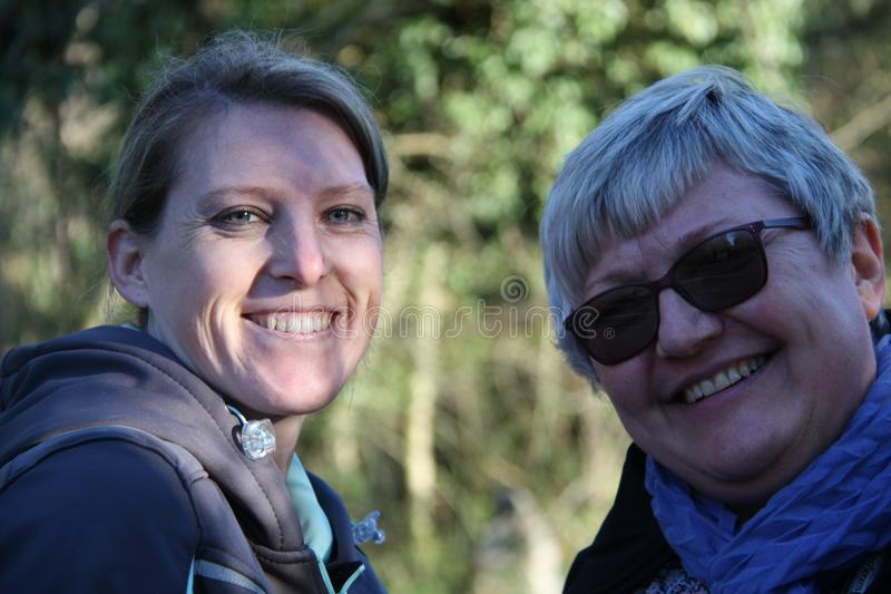 A portrait of two smiling collegue ladies in the nature royalty free stock image