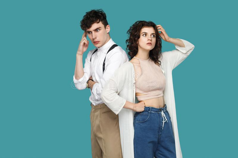 Portrait of two confused thoughtful brunette stylish partner standing, looking away, scratching head and thinking that to do and royalty free stock photos