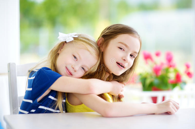 Portrait of two cute little sisters at home on beautiful summer day stock photos