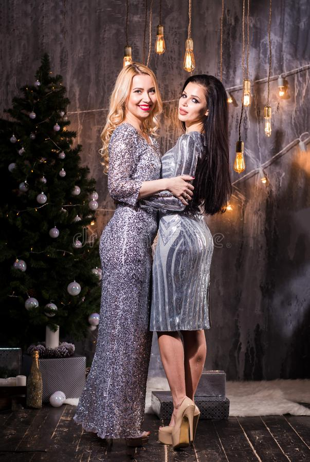 Portrait of two elegant young women near the Christmas tree. Holidays, New Year, celebration and people concept stock photography