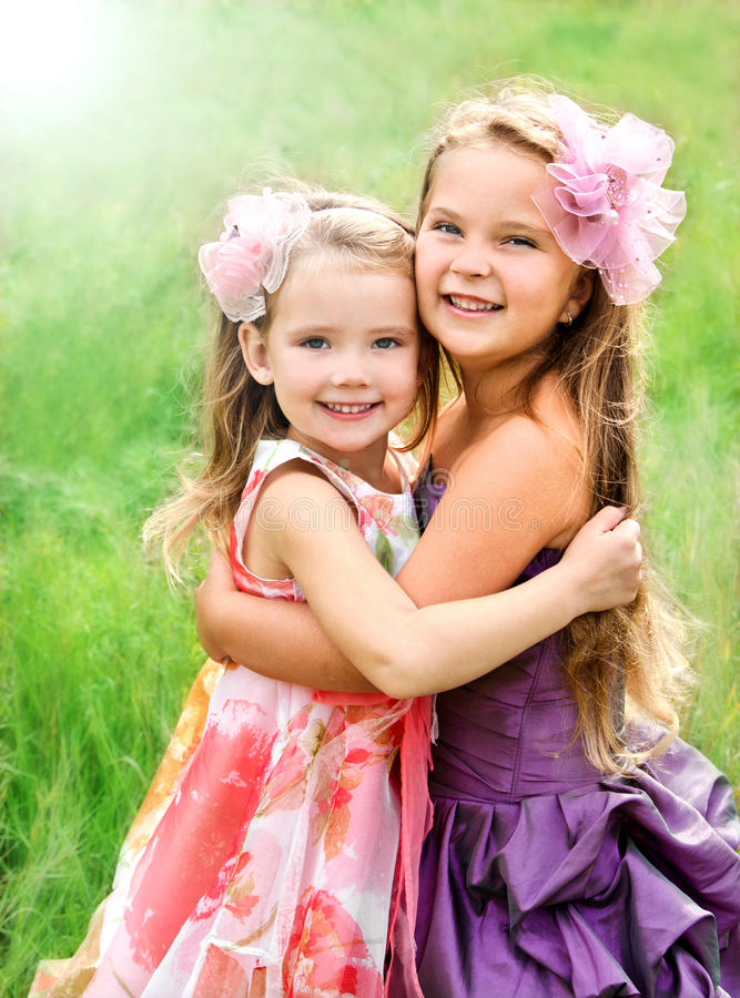 Portrait of two embracing cute little girls royalty free stock image
