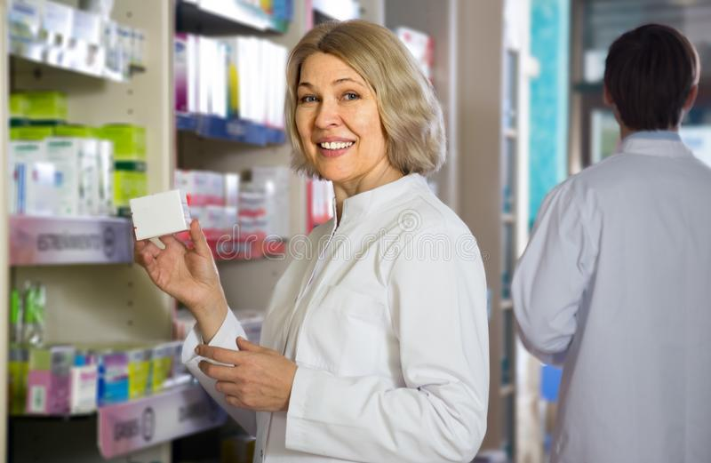 Portrait of two employed pharmacists. Working in modern farmacy royalty free stock photo