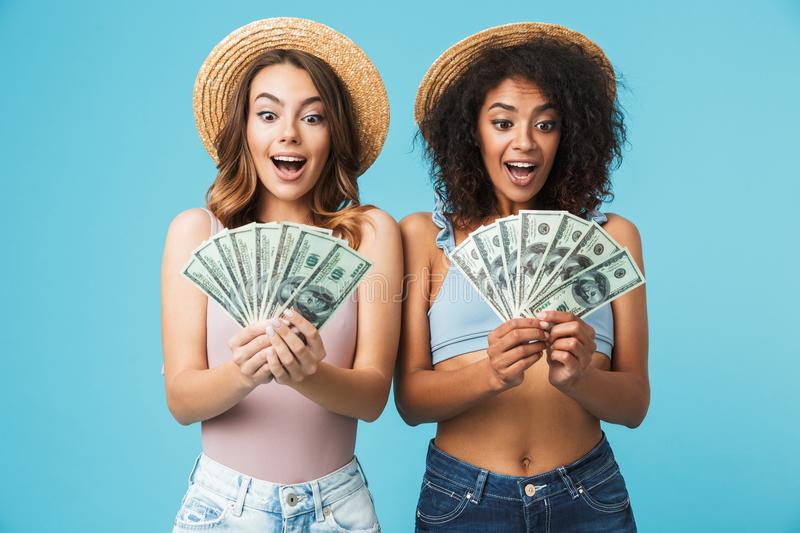 Portrait of two excited women with different type of skin wearing straw hats and summer clothing looking at lots of money holding royalty free stock photography