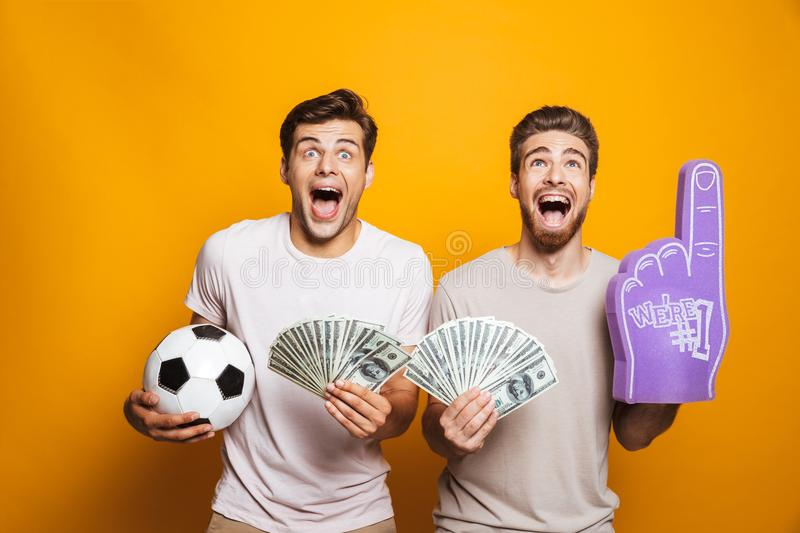 Portrait of a two excited young men best friends. With soccer ball showing money banknotes and shouting isolated over yellow background stock photo