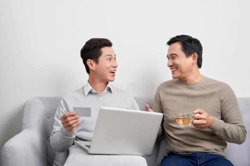 Portrait of a two excited young men holding laptop computer while pointing finger at a credit card and celebrating stock photos