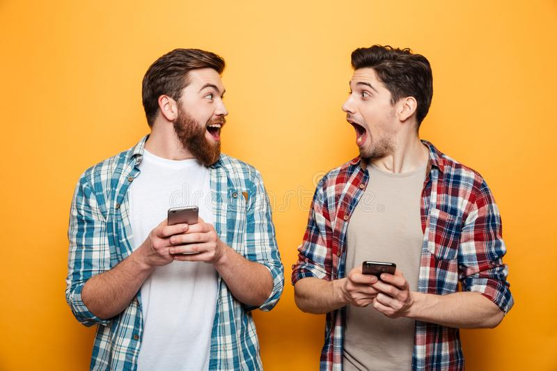 Portrait of a two excited young men holding mobile phones. And looking at each other isolated over yellow background stock photos