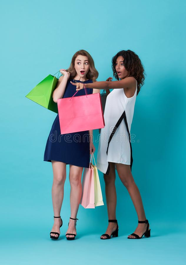 Portrait of two excited young woman hand holding shopping bag and with her finger pointing at copy space over blue background royalty free stock photos