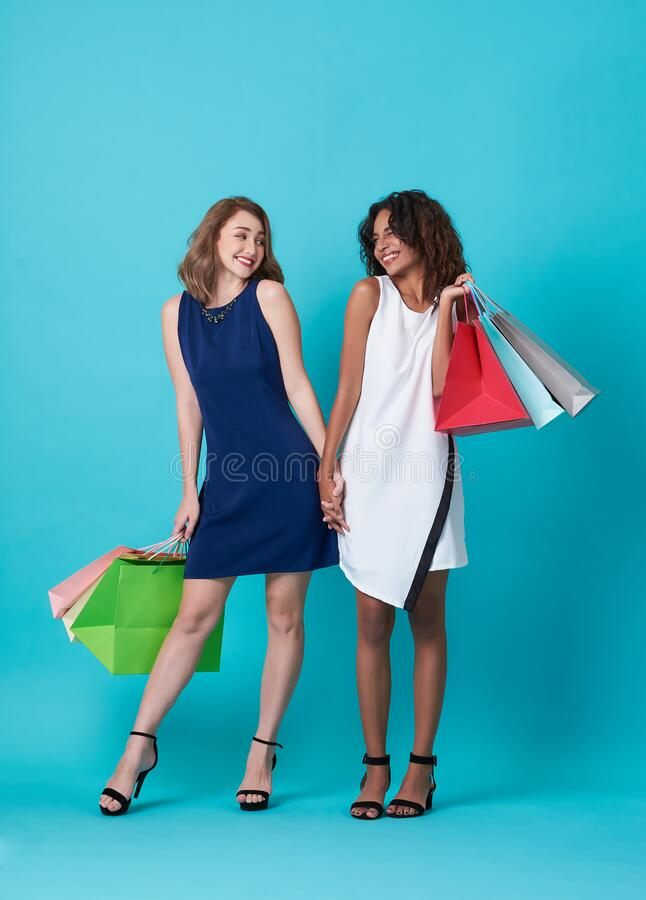 Portrait of two excited young woman hand holding shopping bag over blue background royalty free stock photography